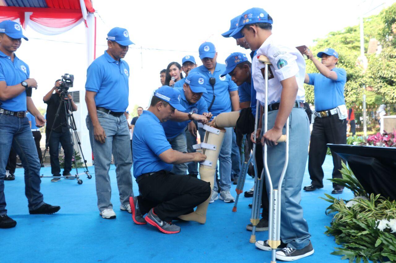 Kapolda Banten Brigjen Pol Listyo Sigit Prabowo sedang memasangkan kaki palsu kepada korban kecelakaan yang kehilangan salah satu kakinya akibat kecelakaan lalu lintas yang dialaminya
